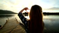 Young woman on lake pier makes hand finger frame on landscape video