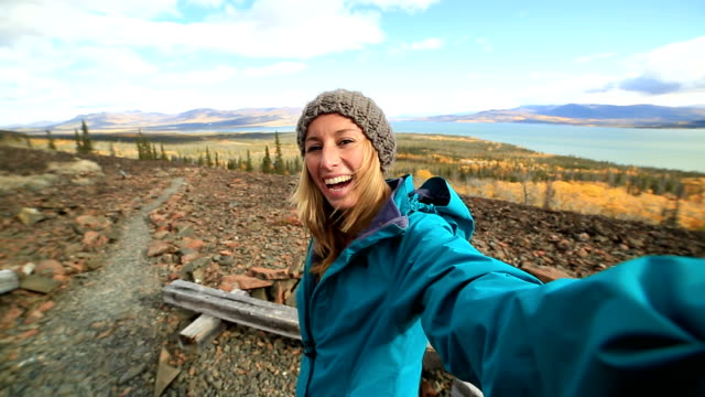Young woman on mountain top taking selfie portrait video