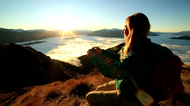 Young woman on mountain top text messaging on mobile phone video