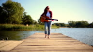 young woman on pier playing  guitar video