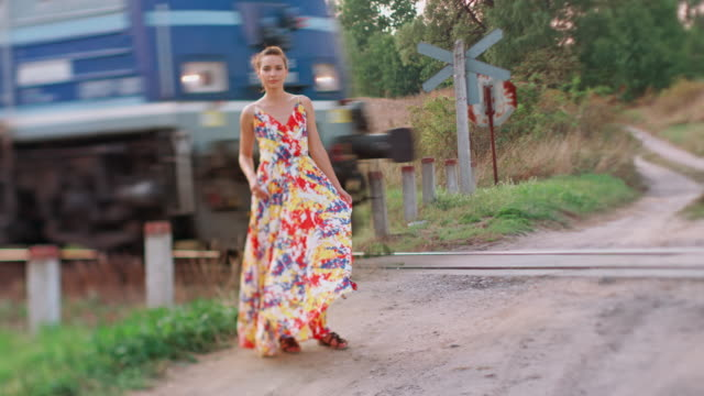 Young woman on railroad crossing video