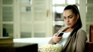 Young woman on sofa watching Television video