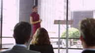 Young woman on stage presenting a business seminar, shot on R3D video