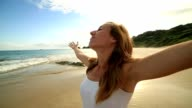 Young woman on the beach arms outstretched for positive emotion video