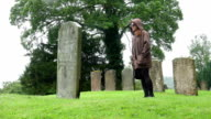young woman on the father tomb in a countryside cemetery in a rainy day: video