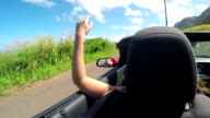 CLOSE UP: Young woman on vacation driving convertible exploring sunny island video