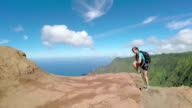 Young woman on vacation hiking up the path in amazing volcanic mountain range video
