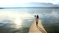 Young woman on wooden jetty taking picture video