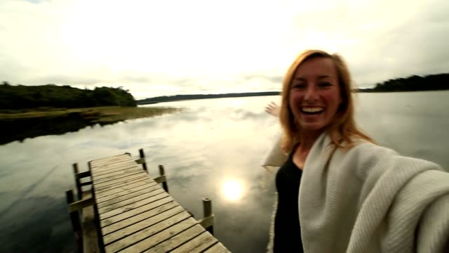 Young woman on wooden wharf above lake, takes selfie portrait video
