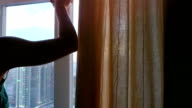 Young woman open the curtains and looks from window to city from top view in slowmotion during beautiful sunset video