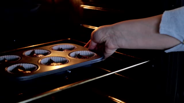 Young woman open the oven and puts on the baking dish with dough. Female cooking the cupcakes in the kitchen video