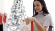Young woman opening a Christmas gift bag video