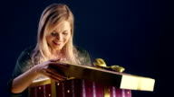 Young woman opening magical Christmas gift video