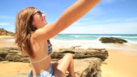 Young woman outstretches arms on beach video