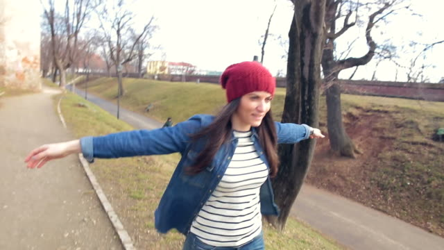 Young woman outstretching her arms while walking in the park. video