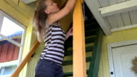 young woman paint with brush wooden column in village room video