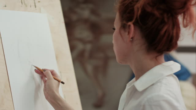 Young woman painter making sketches on blank canvas in artist workshop video