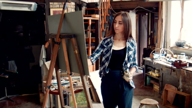Young woman painting a canvas in a studio video