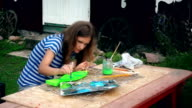 Young woman painting fish decoration on wooden table in house yard video