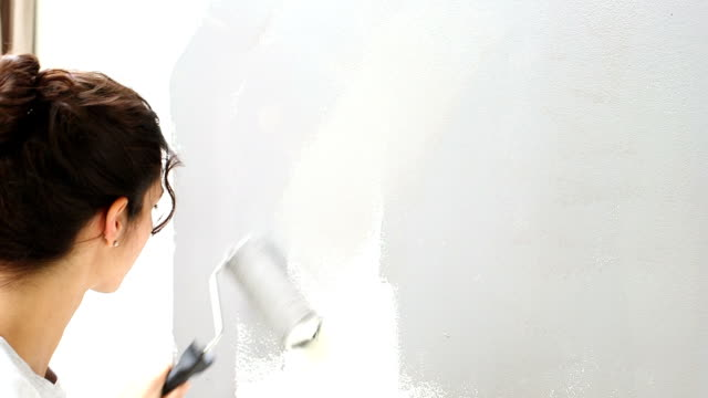 Young woman painting wall with paint roller video