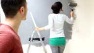 MS Young woman painting wall with paint roller video