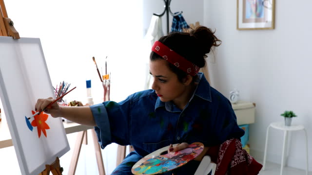 Young woman painting with oil paint video