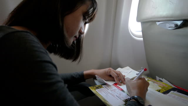 Young Woman passenger Write Immigration Card in Airplane video