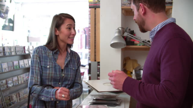 Young woman paying man at the counter of a record shop video