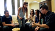Young woman performing during game of charades with family video