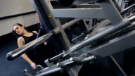 Young woman performing leg presses on a large metal simulator video