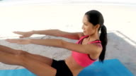 Young woman performing yoga on beach video