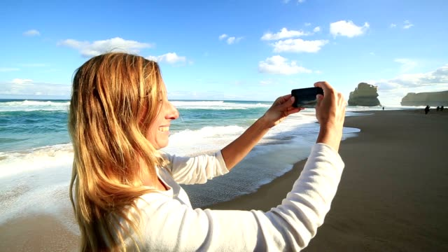 Young woman photographing landscape with mobile phone video