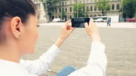 Young woman photographing the city in a beautiful day. video