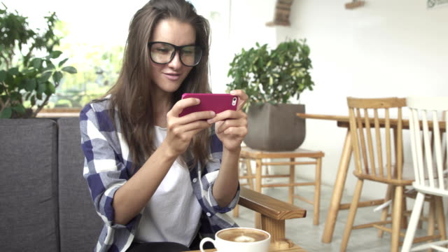 Young woman playing game on smartphone video