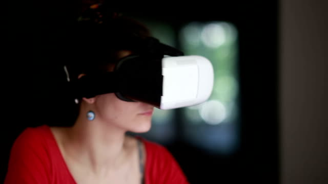 Young woman playing game using VR-helmet video