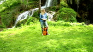 Young woman playing guitar by waterfall in summer video