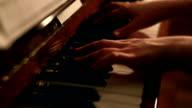 Young woman playing piano close up shot video