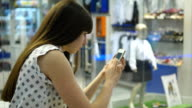 Young woman playing popular smartphone game in mall video