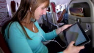 Young woman playing video games on digital tablet while traveling video
