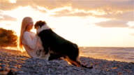 Young woman playing with Australian Shepherd on the shores of a lake or the sea. The sun shines on the beautiful sunset in her hair video