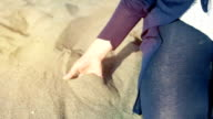 young woman playing with the sand through your fingers at the sea on the beach video