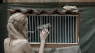 Young woman playing with two pigeons video