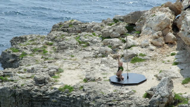 Young woman pole dancer performing pole dance on a rock during outdoor workout video