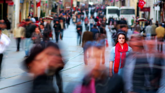 Young woman posing, busy street, people walking around video