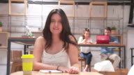 Young woman posing in a small office video