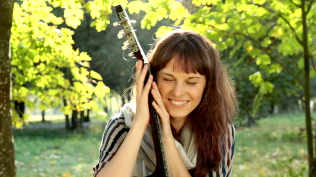 Young woman posing in park, holding guitar, smiling, flirting outdoors. video