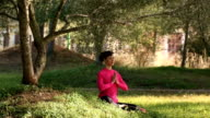 young woman practicing meditation in the park video