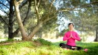 young woman practicing meditation outdoors video
