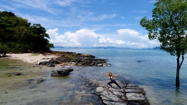 Young woman practicing yoga moves in tropical settings video