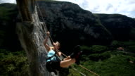 Young woman pulls herself across Tyrolean traverse video